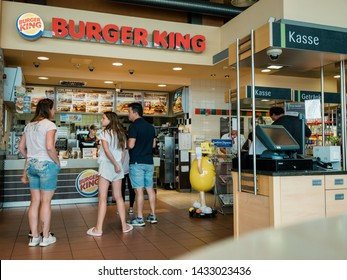 Stuttgart, Germany - Aug 15, 2018: Rear view of traveller family at the counter of Burger King restaurant at Esso gas station in Germany waiting to place the order and get the fast-food away