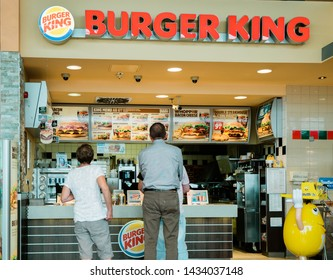 Stuttgart, Germany - Aug 15, 2018: Rear view of senior and adult customers at the counter of Burger King restaurant at Esso gas station in Germany waiting to place the order and get the fast-food away
