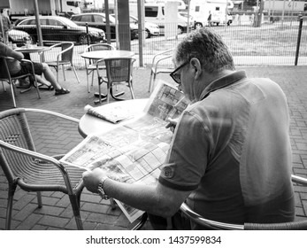 Stuttgart; Germany - Aug 15; 2018: Black and white image of rear view of senior man reading Die Bild newspaper featuring article about Morandi Bridge collapse
