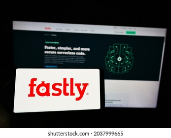 STUTTGART, GERMANY - Aug 23, 2021: Person holding cellphone with logo of US cloud computing company Fastly Inc  on screen in front of business webpage  Focus on phone display