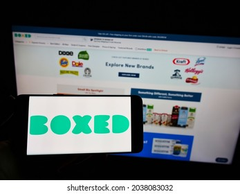 STUTTGART, GERMANY - Aug 30, 2021: Person holding cellphone with logo of company Giddy Inc  (Boxed com) on screen in front of webpage  Focus on phone display