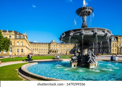 Stuttgart, Germany, August 14, 2019, Beautiful turquoise water in ancient fountain on palace square in front of new castle building, a very popular meeting place for people in summer