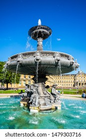 Stuttgart, Germany, August 14, 2019, Azure water in old waterspout fountain at palace square, schlossplatz, in front of new castle building with many people enjoying the public park in summer