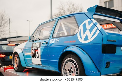 STUTTGART, GERMANY - DEC 2, 2016: Blue Volkswagen GTI racing car on a trailer on the traffic jam in the city of Stuttgart
