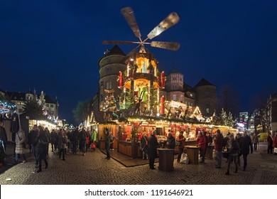 STUTTGART, GERMANY - DECEMBER 14, 2017: Christmas market with Christmas pyramid close to Altes Schloss (Old Castle) in dusk. The Christmas pyramid is a kind of carousel demonstrating nativity scenes.