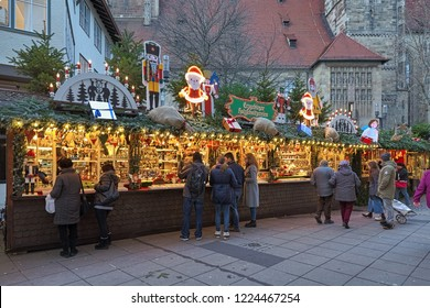 STUTTGART, GERMANY - DECEMBER 14, 2017: Market stalls with Christmas decorations at Christmas market on Kirchstrasse street close to Stiftskirche (Collegiate Church) in evening.