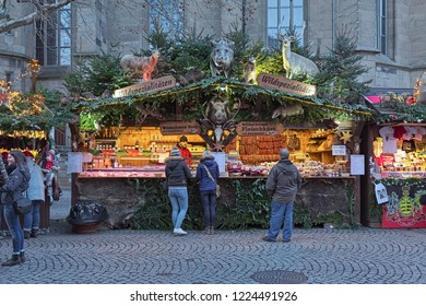 STUTTGART, GERMANY - DECEMBER 14, 2017: Market stall with wild meat specialties at Christmas market close to Stiftskirche (Collegiate Church) in evening.