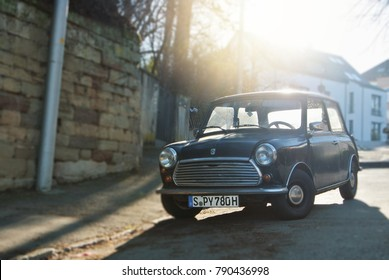 STUTTGART, GERMANY - DECEMBER 29, 2017: Old retro classic vintage oldtimer black mini copper car vehicle standing parked in the street near the stone wall in warm morning light, toned instagram photo.