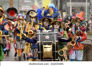 STUTTGART, GERMANY - FEBRUARY 28: bass drum player musician dressed up and walking as a colorful marching band among viewers. Shot at Carnival parade in city center on feb 28, 2017 Stuttgart, Germany