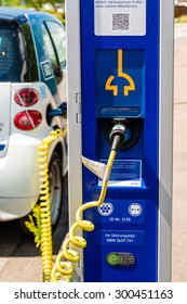 STUTTGART, GERMANY - JULY 25, 2015: An electric Smart of car sharing company car2go is being plugged into a charging station in Stuttgart, Germany. Car2go is a company of the Daimler group