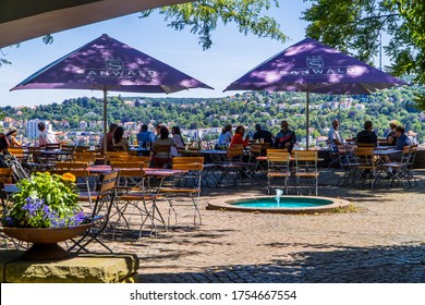 Stuttgart, Germany - June 12, 2020 - people drinking and eating at bar (Biergarten) on the Karlshöhe hills with panoramic Stuttgart city view in the background