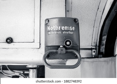 "Stuttgart, Germany - June 7, 2020: Monochrome picture of an emergency brake in a historical tram in Germany. ""Notbremse - Missbrauch strafbar"" is German for ""Emergency brake - abuse punishable"""