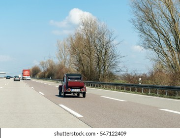 STUTTGART, GERMANY - MAR 26, 2016: POV point of iew of driver looking at Citroen 2CV vintage car driving on autobah on a calm spring day. The Citroen 2CV (French: deux chevaux i.e. deux chevaux-vapeur
