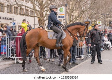 STUTTGART, GERMANY - MARCH 5 2019: policewoman on horseback of sorrel horse opening the parade. Shot under light rain at Carnival parade in city center on march 5, 2019 Stuttgart, Germany