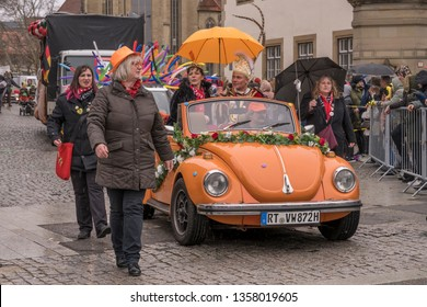 STUTTGART, GERMANY - MARCH 5 2019: vintage orange convertible with dressed up participants under rain. Shot at  Carnival parade in city center on march 5, 2019 Stuttgart, Germany