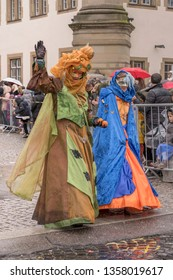 STUTTGART, GERMANY - MARCH 5 2019: two dame dressed up participants in parade under light rain.  Shot at  Carnival parade in city center on march 5, 2019 Stuttgart, Germany