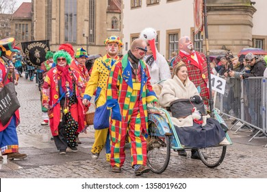 STUTTGART, GERMANY - MARCH 5 2019: group of clown  masks with an hand-cart  in parade under light rain.  Shot at  Carnival parade in city center on march 5, 2019 Stuttgart, Germany