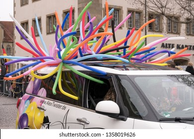 STUTTGART, GERMANY - MARCH 5 2019: car with bunch of colorful balloons over roof . Shot under rain at  Carnival parade in city center on march 5, 2019 Stuttgart, Germany