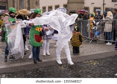 STUTTGART, GERMANY - MARCH 5: group of participants wrapping up against wet. Shot under rain at  Carnival parade in city center on march 5, 2019 Stuttgart, Germany