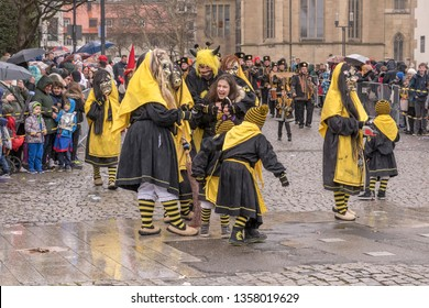 STUTTGART, GERMANY - MARCH 5: group of ugly dressed up witches act with terrified girl while parading under light rain. Shot  at  Carnival parade in city center on march 5, 2019 Stuttgart, Germany