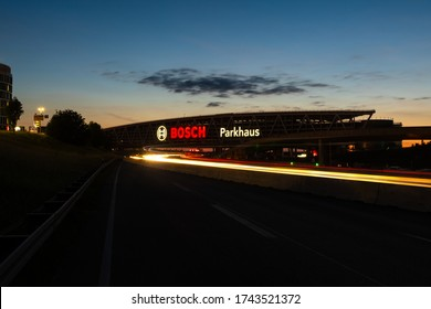 Stuttgart, Germany - May 26, 2020: Huge Bosch letters at the Stuttgart Airport parking garage with long exposure of highway A8 at dusk. Bosch is a German multinational engineering and electronics