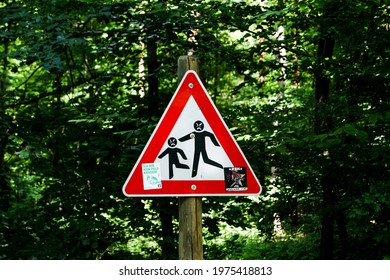 """Stuttgart, Germany - May 31, 2020:  A defaced triangle warning sign """"Attention playing children"""" in the forest. The children now look angry."""