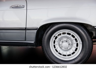 STUTTGART, GERMANY - OCTOBER 16, 2018: Mercedes Museum. Side close up view of white retro car with white light alloy wheel and low-profile tire, chrome disk, arch above.
