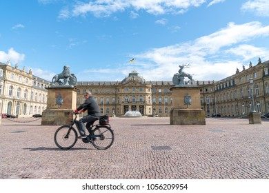 STUTTGART, GERMANY - SEPTEMBER 13; Blurry image of man cycling past large cobblestone courtyard surrounded by historic building September 13 2017 Stuttgart Germany