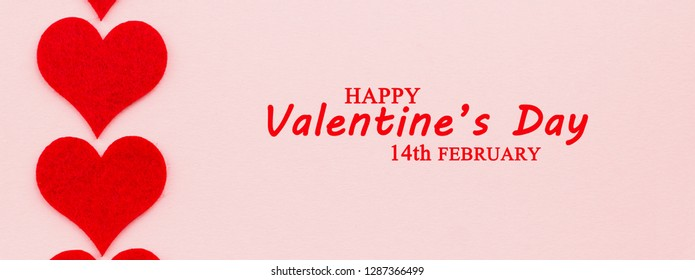 St.Valentine's Day holiday background. Red hearts in a shape of a heart on pink background. Flat lay. View from above with text Happy Valentine's Day and 14th February.