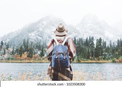 Styish woman feeling happy among amazing mountains, enjoy the nature landsape. Forest and lake, wearing backpack, hat and poncho, boho and wanderlust style