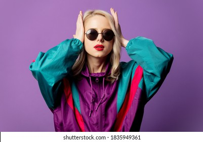 Style blonde in 80s windbreaker and roud sunglasses on purple background