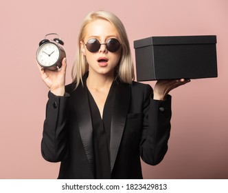 Style blonde in blazer and sunglasses with black gift box and alarm clock on pink background