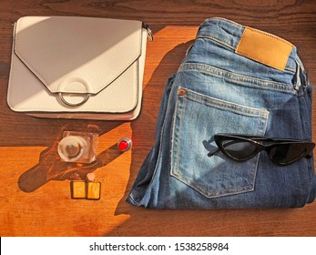 Style concept. Fashion flatlay. Jeans, white crossbody bag, perfume, sunglasses, red lipstick, earrings on wooden background