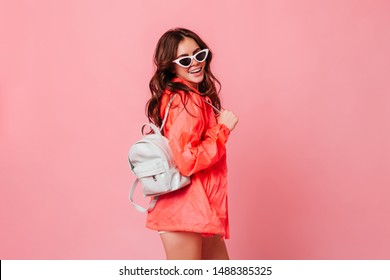Style curly brunette woman in sunglasses smiles. Lady in windbreaker holding white leather backpack