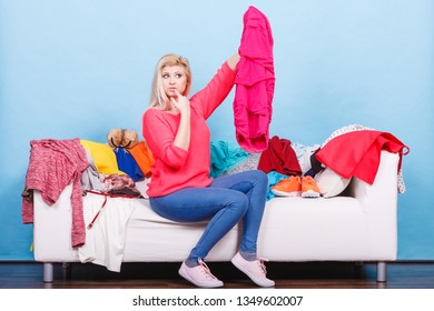 Style dilemmas concept. Woman does not know what to wear sitting on messy couch with piles of clothes and looking through clothing.