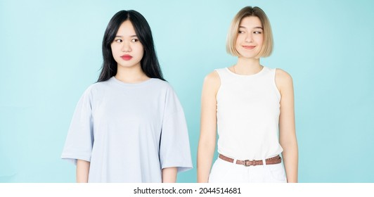 Style diversity. Female friendship. Inconvenient situation. Curious smiling asian and caucasian women spying each other isolated blue.