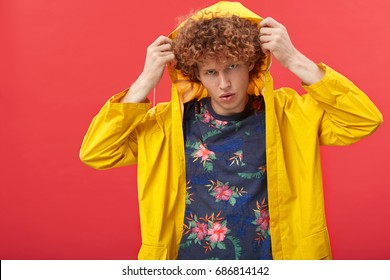 Style and fashion concept. Studio shot of attractive red-haired young male European model wearing stylish clothes, putting on hood of his trendy raincoat, posing isolated against blank wall background