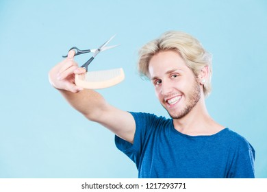 Style and fashion. Young trendy male hairstylist barber with new idea of look changing. Blonde guy with scissors and wooden comb creating hairdo coiffure, on blue