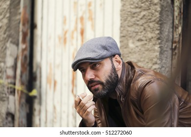 style guy. Fashion man standing near a wooden door and smoking