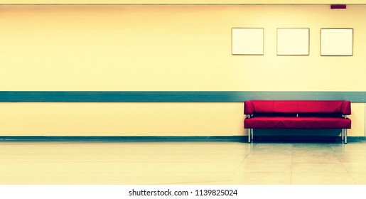 Style minimalism. Red Sofa, interior design, office. Empty waiting room with a modern red sofa in front of the door and three empty frames on the wall