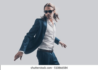 Style in motion. Handsome young man in full suit and sunglasses moving in front of grey background