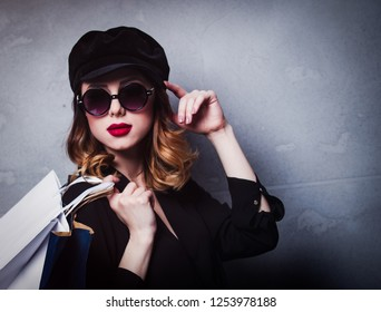 Style redhead girl in hat with shopping bags and sunglasses on grey background
