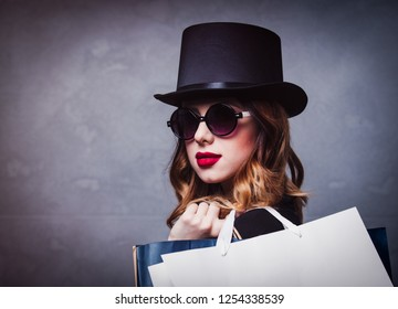 Style redhead girl in top hat with shopping bags on grey background