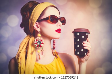 Style redhead woman in yellow clothes with coffee. Photo with bokeh on background.