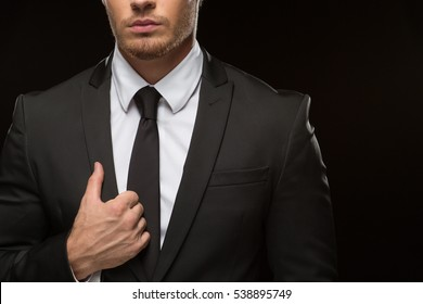 Style speaks louder than words. Cropped shot of a well dressed man posing in a formal suit over black background copyspace on the side