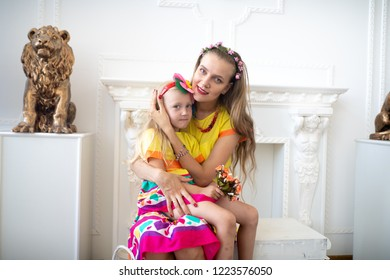 Style summer family look. Mom and daughter love. Take care of the child and ensure a happy childhood. Fun holidays. Bright yellow pink dress and floral decorations. White professional studio banner