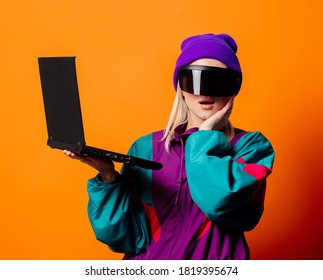 Style woman in 90s tracksuit and VR glasses with notebook on orange background