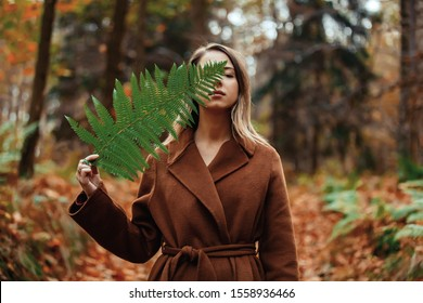 Style woman with fern branch in a autumn time forest