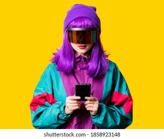 Style woman in VR glasses and 80s tracksuit with mobile phone on yellow background
