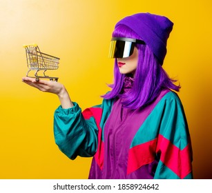 Style woman in VR glasses and 80s tracksuit with shoping cart on yellow background